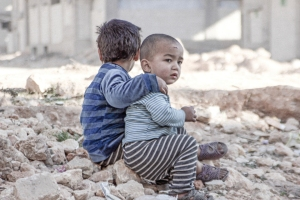 On 25 December 2015 in Aleppo in the Syrian Arab Republic, (left) Esraa, 4, and (right) her brother Waleed, 3, sit on the ground near a shelter for internally displaced persons.